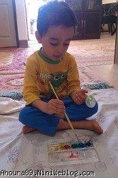 پسری در حال رنگ کردن تخم مرغ