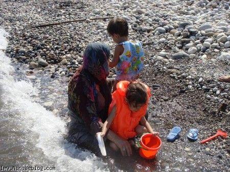ایلیا در حال در رفتن از دست مامانی وقتی مامانی از ترس دریا هر دو را محکم گرفته است